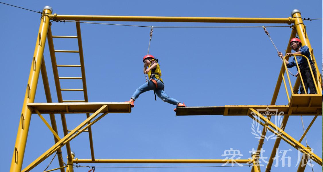 接下来我们要做的一个项目叫做断桥,这是一个个人心理挑战的项目,我们队的每一个队员都要在穿戴好安全保护的装备后,从铁柱爬上断桥,站在木板的一端奋力跳向另一端,跳过之后再跳回来,就完成了这个任务。