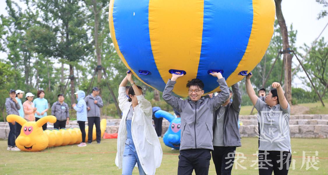 运转乾坤三夫拓展是一种趣味团队运动项目,此团建活动是团队成员举起充气大气球齐力向终点跑去,途中气球不可落地。速度最快的团队获胜。
