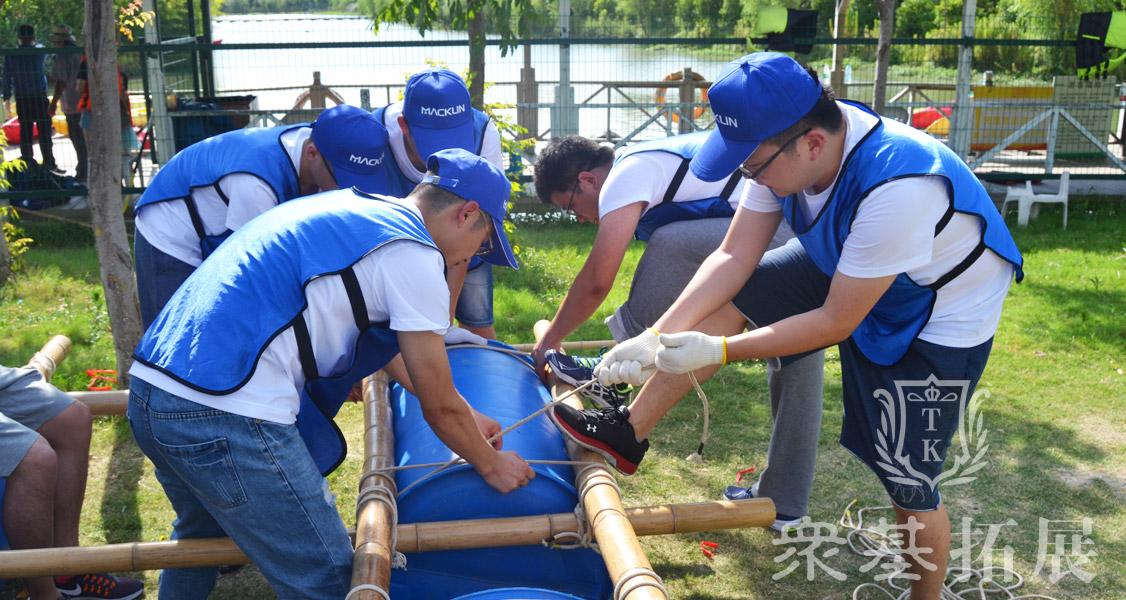 团队队员利用有限的资源(油桶、竹竿、绳子),以最快的速度造成一艘船,搭载本队队员在规定时间内划过规定水域夺得对岸的目标。